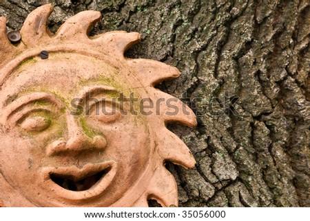 Terracotta sun face on oak tree - stock photo