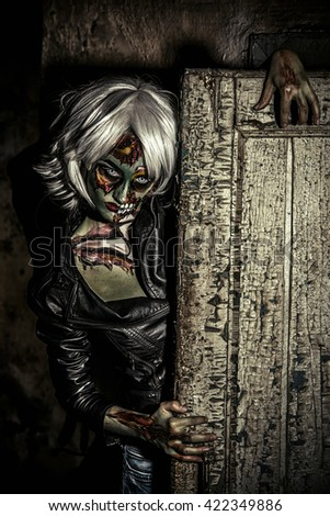 Terrible bloodthirsty zombie woman in the slums. Body-painting project. Glamorous zombie girl. Halloween make-up. Horror. - stock photo