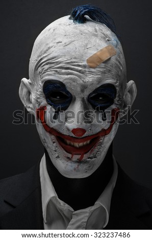 Terrible clown and Halloween theme: Crazy terrible blue clown in black suit isolated on a dark background in the studio - stock photo