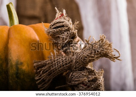Terrible cross shaped Halloween burlap magical puppet near orange segmented squash with green blotch on white and brown cloth background, horizontal picture