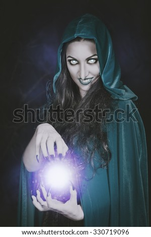 Terrible halloween witch with fireball in her hands - stock photo