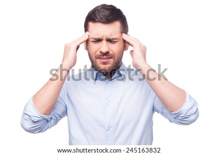 Terrible headache. Young man in shirt touching his head and keeping eyes closed while standing against white background - stock photo