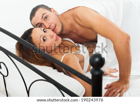 Terrified lovers caught during adultery in bed - stock photo