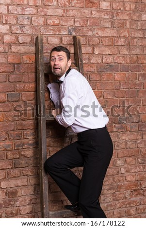 Terrified man trapped at the top of a ladder cowering against the brick wall with an expression or dread and fear