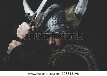 Terrified, Viking warrior with iron sword and helmet with horns - stock photo