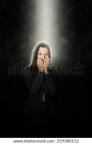 Terrified woman standing in a beam of white light shining down through the darkness from above looking at the camera with terror in her eyes and biting her nails in suspense - stock photo