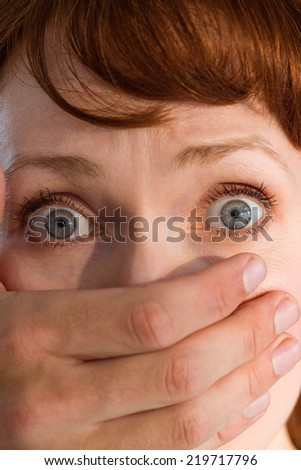 Terrified woman with covered mouth on black background - stock photo