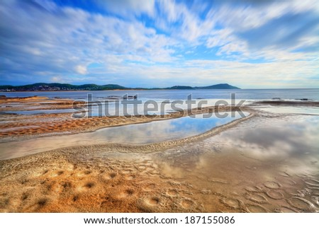 Terrigal Haven, looking towards Terrigal and Wamberal, NSW Australia.  Water reflections and the beginnings of crater erosion. Motion  Focus to foreground  Long exposure 17sec - stock photo