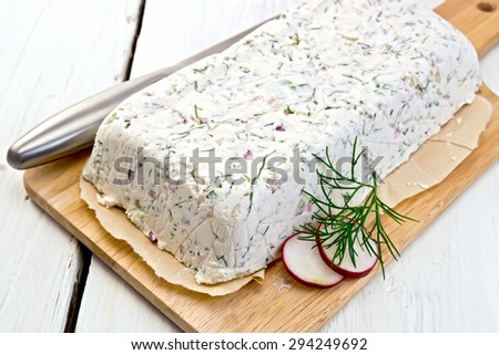 Terrine of curd and radish with dill, chives, knife on paper and board on a light wooden planks - stock photo