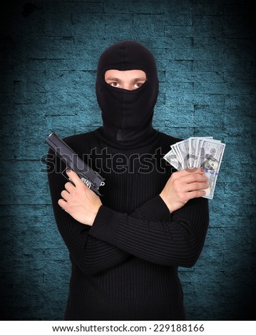 terrorist holding gun and dollars on blue background - stock photo