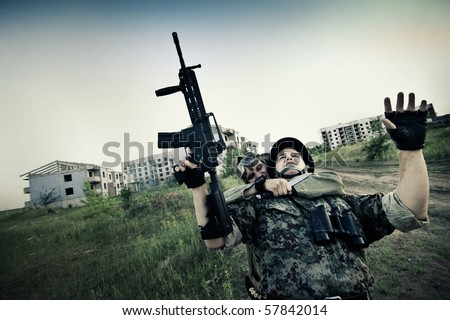 Terrorist is catching a soldier as a hostage. Cross processing styled. - stock photo