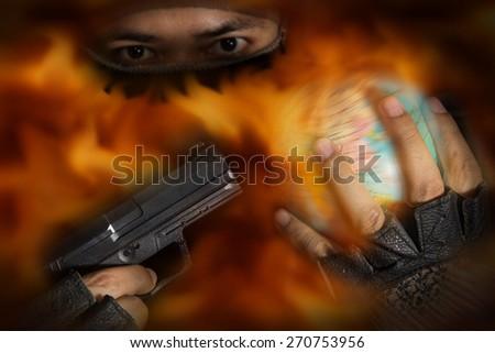 Terrorist put a gun to globe with fire flame screen. - stock photo