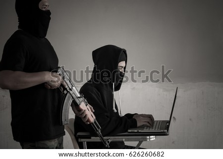 Terrorist team with anonymous hacker stealing data from laptop. Cyber security concept.