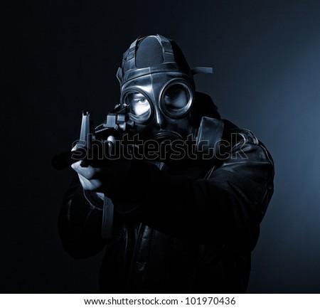 terrorist with gasmask dark background - stock photo