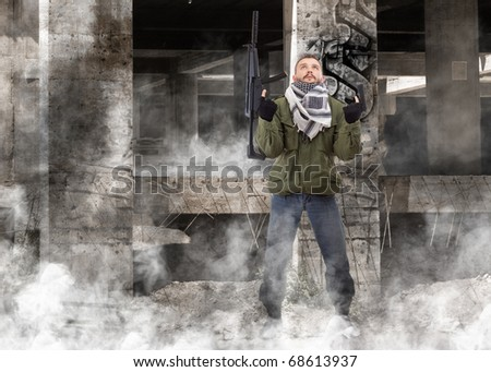 Terrorist with rifle, grunge buildings in background - stock photo