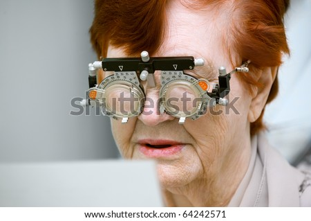 Test examination of an elderly woman at an optician clinic - stock photo