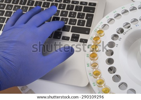 test lab for analysys - keyboard and test tube holeder with gloved hand - stock photo