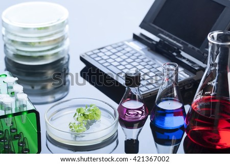 test tube retotr and green sprout in lab - stock photo