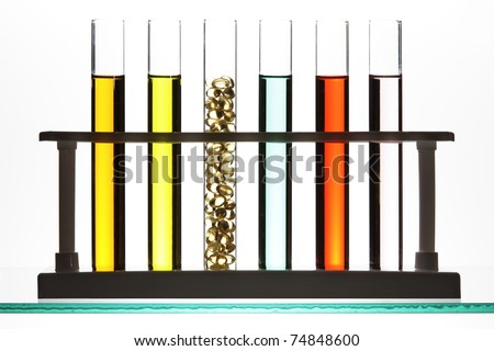 Test tubes filled with colored fluid, one filled with gel cap vitamins. - stock photo