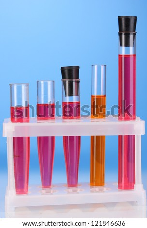 Test-tubes with a colorful solution on blue background close-up