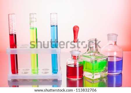 Test tubes with color liquid on red background - stock photo