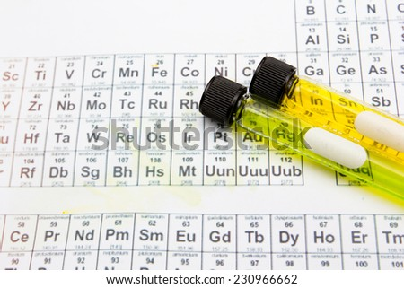 test tubes with colored reagents on the periodic table - stock photo