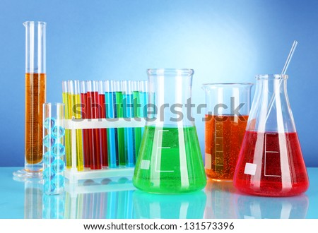 Test tubes with colorful liquids on blue background - stock photo