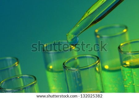 test-tubes with liquid on blue background - stock photo