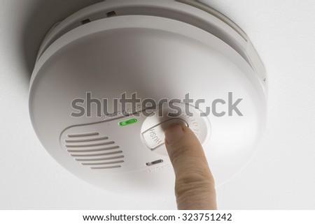 Testing a home smoke alarm - stock photo