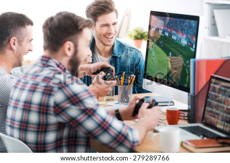 Testing new game. Three young men playing computer games while sitting at the desk in the office - stock photo