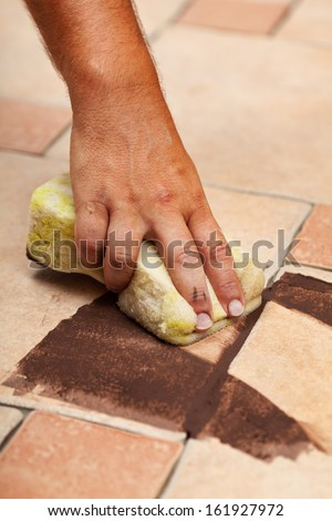 Testing the color of joint on ceramic floor tiling - closeup on hand - stock photo