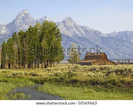 Teton Farm along Mormon Row, Antelope Flats, Grand Teton National Park, Wyoming with snow-capped Teton Mountain Range behind - stock photo