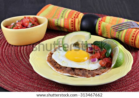 Tex Mex Huevos Rancheros, with pico de gallo, sliced avocado on a tortilla with refried beans.
