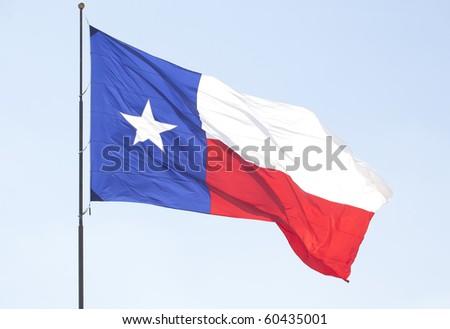 Texas Lone Star flag pole flying over the blue sky . - stock photo