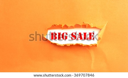 Text BIG SALE appearing behind torn paper - stock photo