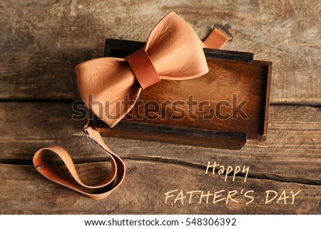Text HAPPY FATHER'S DAY on background. Gift on wooden table