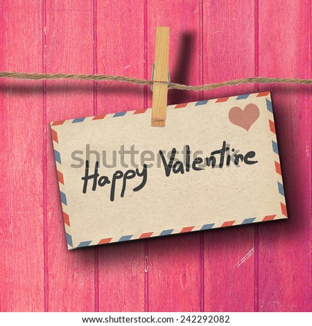 TEXT Happy Valentine on the old envelep and clothes peg wood background - stock photo