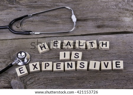 Text: HEALTH IS EXPENSIVE from wooden letters on wooden background - stock photo