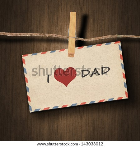 text I love dad on the old envelope and clothes peg wood background - stock photo