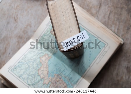 "text ""Just go"" book and map. Travel and tourism concept."