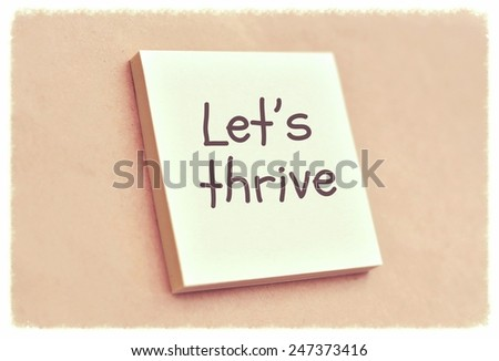 Text let's thrive on the short note texture background - stock photo