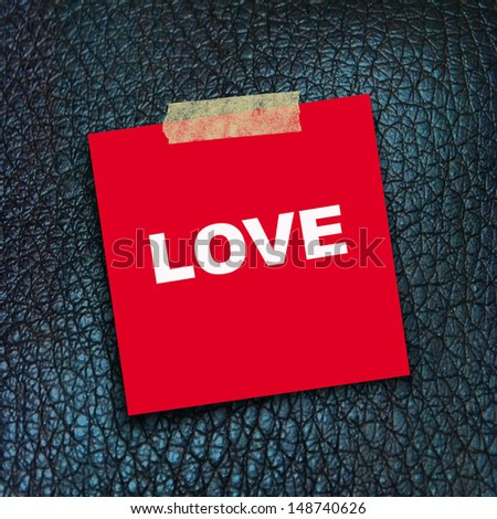 text LOVE  on red  short note paper on sneak skin texture background