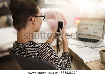 Text messaging woman in front of her laptop - stock photo