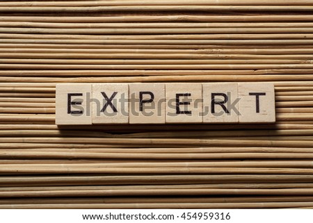 text of EXPERT on wood abc cubes at wooden background