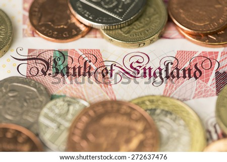 Text of UK currency bank note surrounded by UK currency coins - stock photo