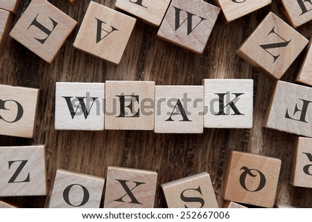 text of WEAK on cubes - stock photo