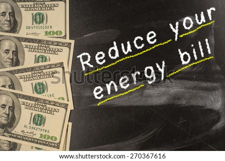 Text on blackboard with money - Reduce your energy bill - stock photo