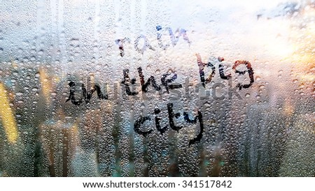 """Text """"rain in the big city"""" written on the wet window in the big city - stock photo"""