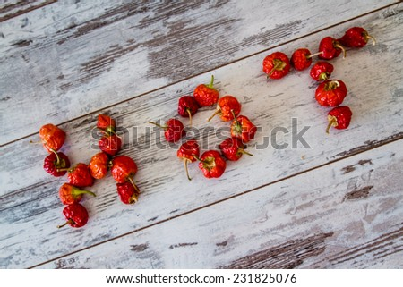 """Text """"Red"""" written by red hot cherry peppers over white wooden background - stock photo"""