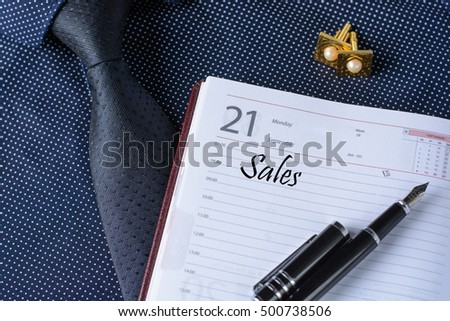 Text Sales and business accessories (cufflinks, fountain pen, tablet, phone, notepad, dairy) in the men's classic shirt with tie